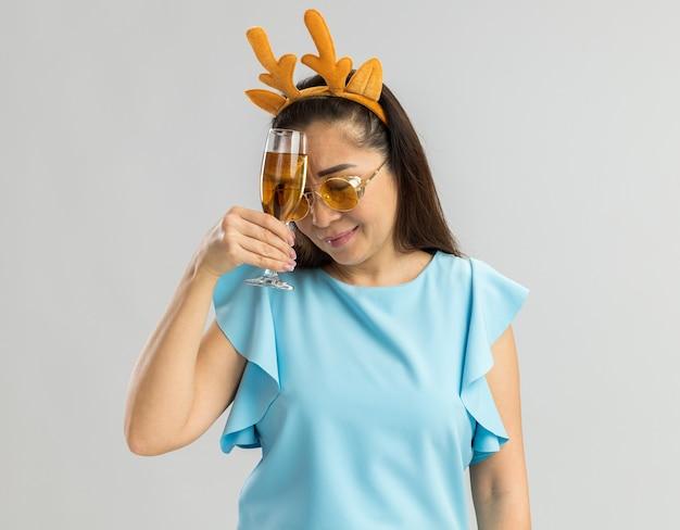 Jonge vrouw in blauwe bovenkant die grappige rand met herten hoorns en gele glazen dragen die glas champagne houden die vermoeid en verveeld kijken