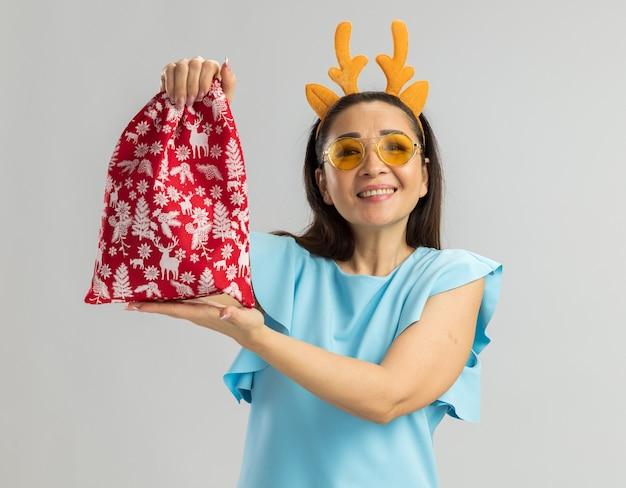 Jonge vrouw in blauwe bovenkant die grappige rand met hertenhoorns en gele glazen draagt die kerstmis rode zak houden die vrolijk glimlachen kijkt