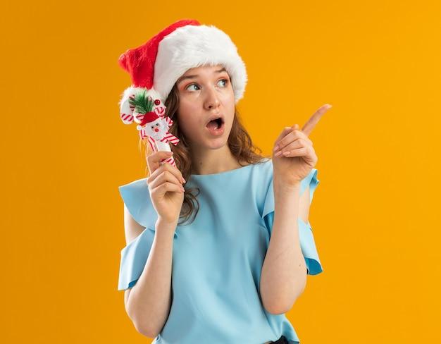 Jonge vrouw in blauwe bovenkant en kerstmuts met kerst candy cane opzij kijken verrast wijzend met wijsvinger naar iets