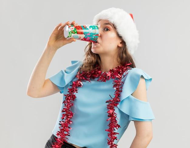 Jonge vrouw in blauwe bovenkant en kerstmuts met klatergoud om haar nek drinken uit kleurrijke papieren beker