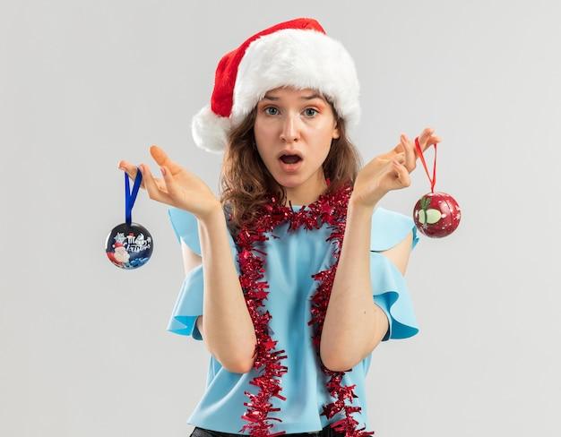 Jonge vrouw in blauwe bovenkant en kerstmuts met klatergoud om haar nek met kerstballen op zoek verward en verrast