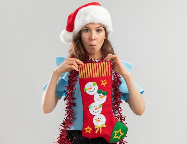 Jonge vrouw in blauwe bovenkant en kerstmuts met klatergoud rond haar nek met kerstsok op zoek verward en verrast