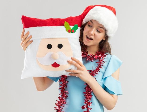 Jonge vrouw in blauwe bovenkant en santahoed met klatergoud om haar hals die het kerstmishoofdkussen met glimlach op gezicht bekijkt