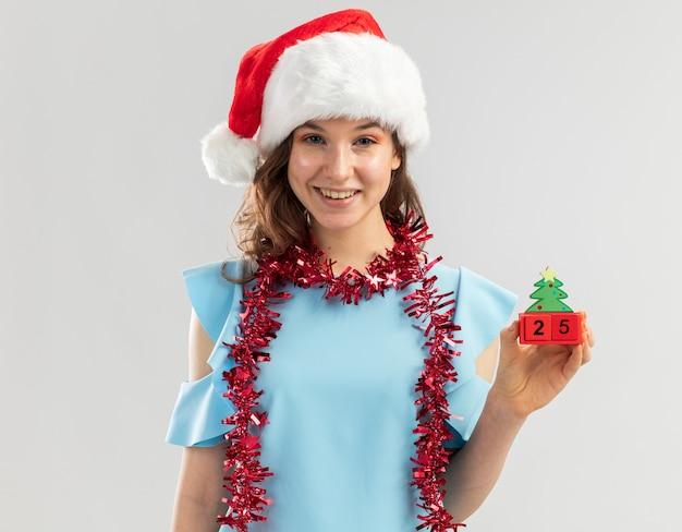 Jonge vrouw in blauwe bovenkant en santahoed met klatergoud rond haar hals die stuk speelgoed kubussen met kerstmisdatum glimlachen die vrolijk kijken