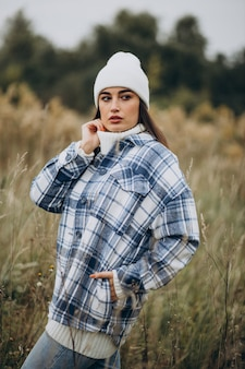 Jonge vrouw in blauwe jas en witte hoed wandelen in herfstbos