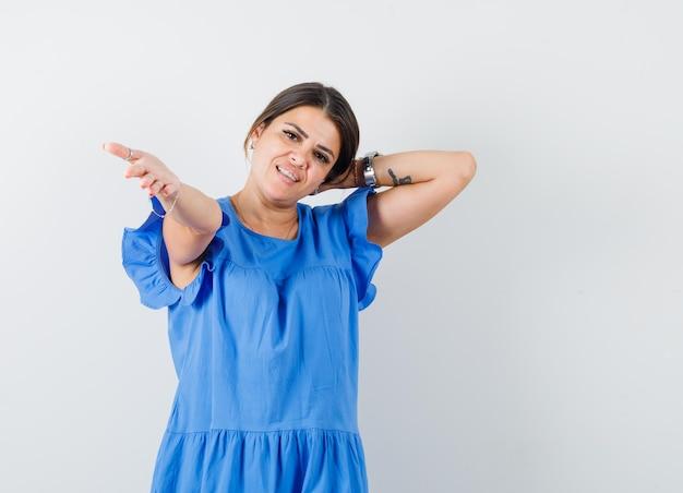 Jonge vrouw in blauwe jurk die de hand uitstrekt, de andere hand achter het hoofd houdt en er schattig uitziet