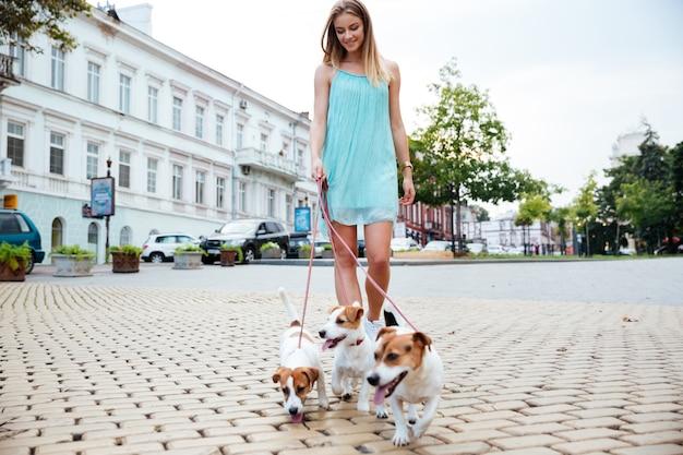 Jonge vrouw in blauwe jurk die haar honden meeneemt voor een wandeling op straat