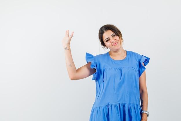 Jonge vrouw in blauwe jurk die met de hand zwaait om afscheid te nemen en er vrolijk uitziet