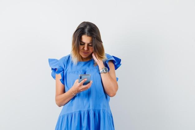 Jonge vrouw in blauwe jurk die mobiele telefoon gebruikt en er druk uitziet