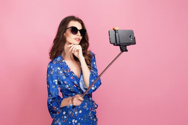 Jonge vrouw in blauwe jurk en zonnebril die selfie nemen