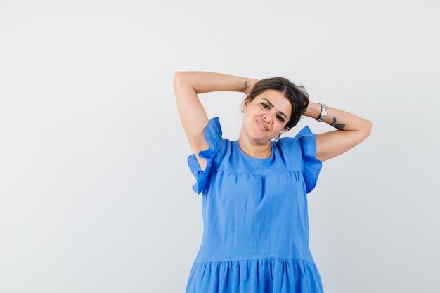 Jonge vrouw in blauwe jurk hand in hand achter het hoofd en ziet er ontspannen uit