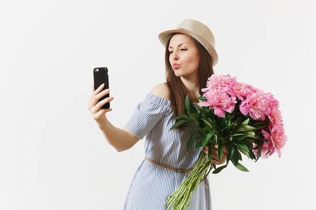 Jonge vrouw in blauwe jurk, hoed met boeket van mooie roze pioenrozen bloemen, selfie doen op mobiele telefoon geïsoleerd op een witte achtergrond. st. valentijnsdag, internationale vrouwendag vakantie concept.