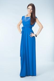Jonge vrouw in blauwe jurk poseren in studio