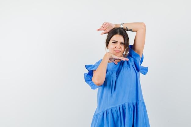 Jonge vrouw in blauwe jurk poseren met de hand onder de kin en ziet er mooi uit