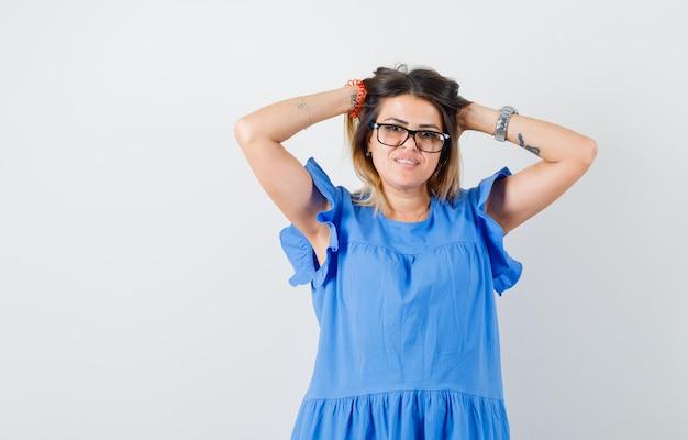 Jonge vrouw in blauwe jurk poseren terwijl ze haar hoofd omklemt en er mooi uitziet