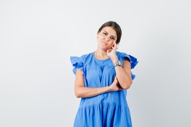 Jonge vrouw in blauwe jurk staat in denkende houding en ziet er verstandig uit