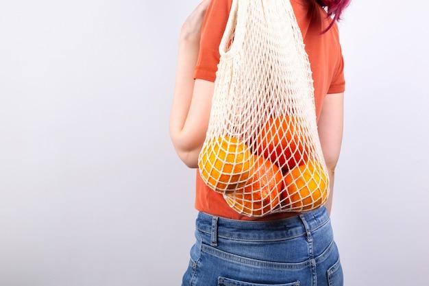 Jonge vrouw in blauwe spijkerbroek en oranje t-shirt houdt string tas met verschillende citrus op grijze achtergrond.