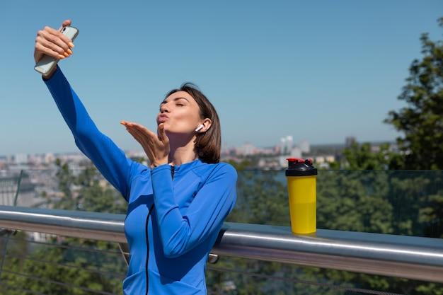 Jonge vrouw in blauwe sportkleding op brug op warme zonnige ochtend met draadloze koptelefoon en mobiele telefoon, selfie fotovideo nemen voor socials
