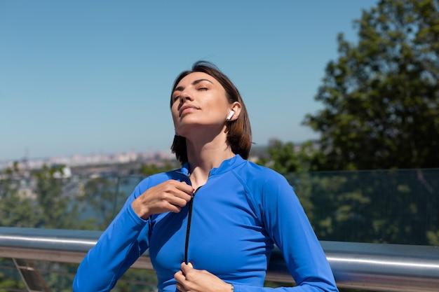 Jonge vrouw in blauwe sportkleding op brug op warme zonnige ochtend met draadloze koptelefoon ritst jas open
