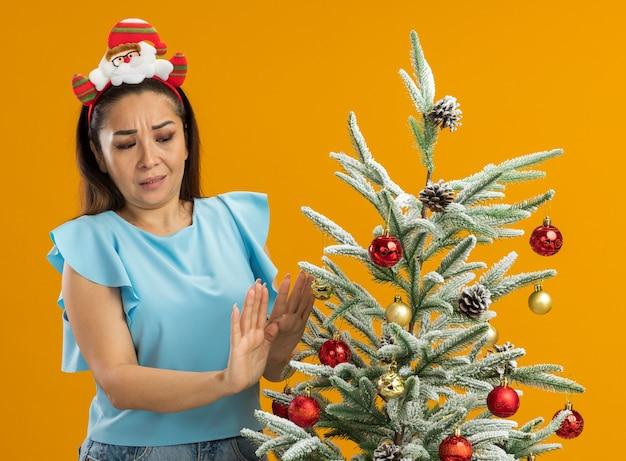 Jonge vrouw in blauwe top die grappige kerstrand op haar hoofd draagt ?? die naast een kerstboom staat en ernaar kijkt met verwarde uitdrukking hand in hand over oranje achtergrond
