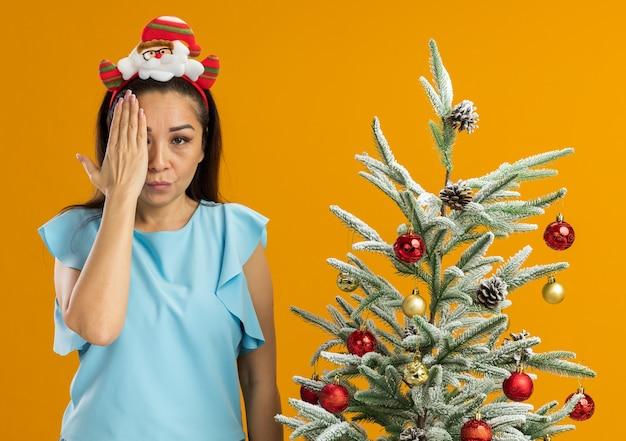 Jonge vrouw in blauwe top die grappige kerstrand op het hoofd draagt en kijkt naar de camera met een ernstig gezicht dat een oog bedekt met een hand die naast een kerstboom staat op een oranje achtergrond