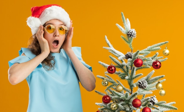 Jonge vrouw in blauwe top en kerstmuts met een gele bril, verbaasd en verrast naast een kerstboom over een oranje muur