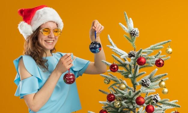 Jonge vrouw in blauwe top en kerstmuts met gele bril met kerstballen blij en vrolijk met een grote glimlach op het gezicht staande naast een kerstboom over oranje achtergrond