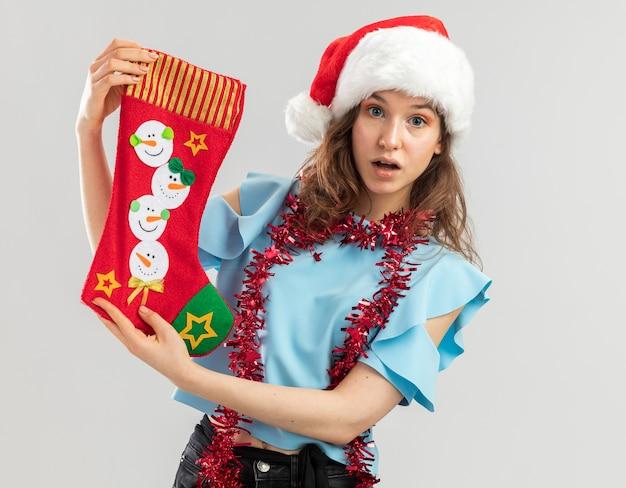 Jonge vrouw in blauwe top en kerstmuts met klatergoud om haar nek met kerstsok verrast over een witte muur