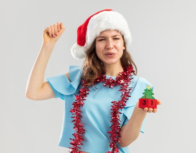 Jonge vrouw in blauwe top en kerstmuts met klatergoud om haar nek met speelgoedblokjes met gelukkige ney-jaardatum gebalde vuist blij en opgewonden