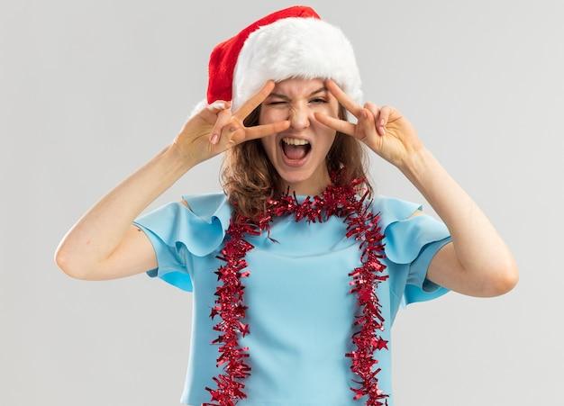 Jonge vrouw in blauwe top en kerstmuts met klatergoud om haar nek op zoek gek, blij en opgewonden met v-teken in de buurt van ogen