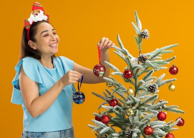 Jonge vrouw in blauwe top met grappige kerstrand op haar hoofd staande naast een kerstboom met kerstballen op zoek naar een boom die vrolijk lacht over oranje achtergrond