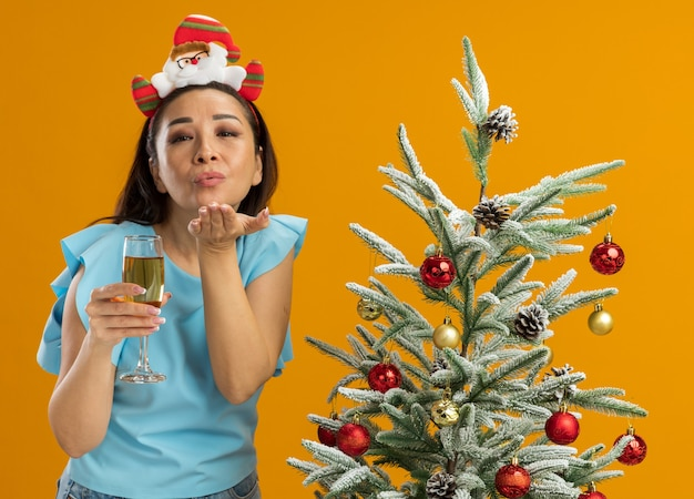Jonge vrouw in blauwe top met grappige kerstrand op het hoofd met glas champagne en blaast een kus gelukkig en positief naast een kerstboom over oranje muur