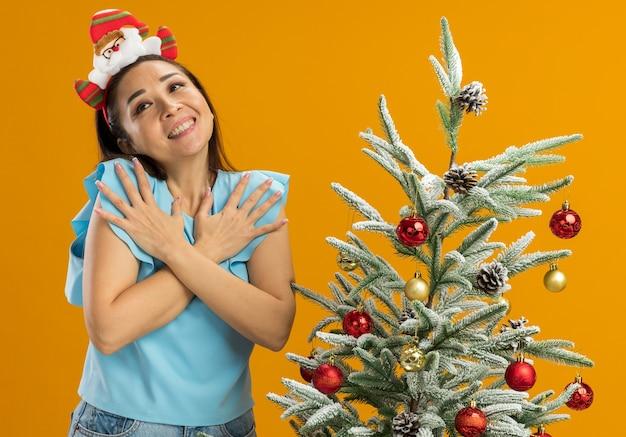 Jonge vrouw in blauwe top met grappige kerstrand op het hoofd staande naast een kerstboom hand in hand op de borst feling dankbaar lachend over oranje achtergrond