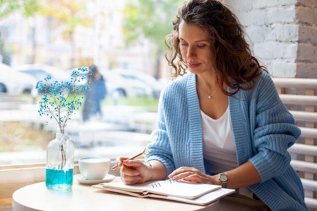 Jonge vrouw in blauwe warme trui zit in de buurt van het grote raam van de coffeeshop en het schrijven van notities