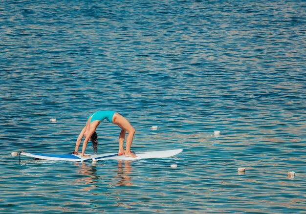 Jonge vrouw in blauwe zwembroek doet yoga op een bord met peddel