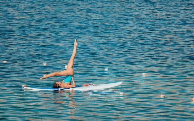 Jonge vrouw in blauwe zwembroek doet yoga op sup bord met peddel.