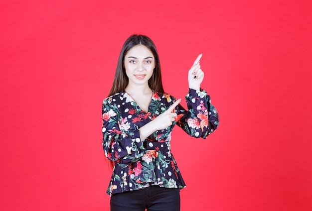 Jonge vrouw in bloemenoverhemd die zich op rode muur bevindt en bovenkant toont