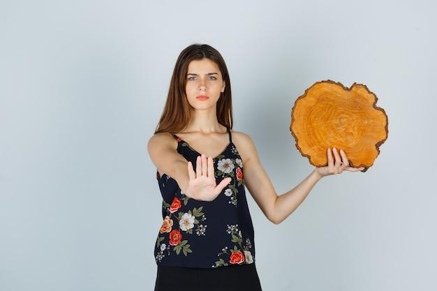 Jonge vrouw in blouse die een stuk hout vasthoudt, een stopgebaar toont en er serieus uitziet, vooraanzicht.