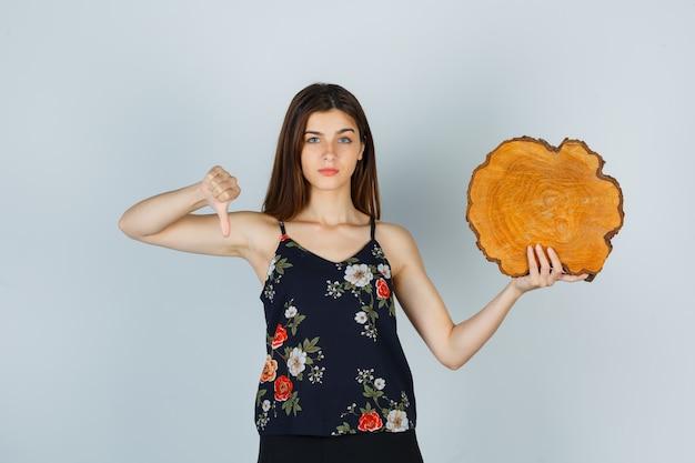 Jonge vrouw in blouse die stuk hout vasthoudt, duim naar beneden laat zien en ontevreden kijkt, vooraanzicht.