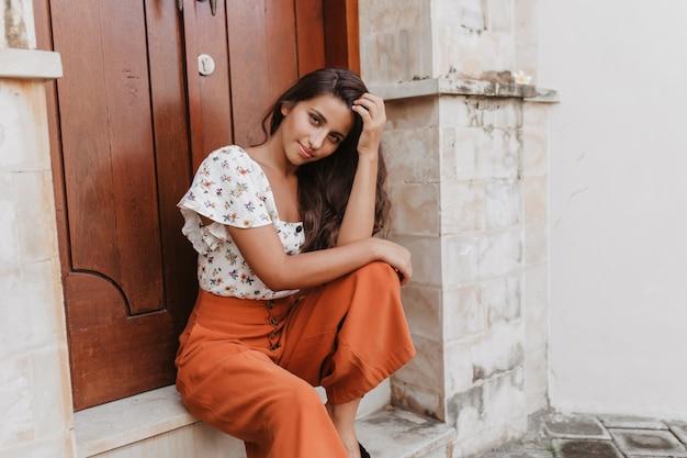 Jonge vrouw in blouse met korte mouwen en stijlvolle broek met hoge taille zit voor de deur