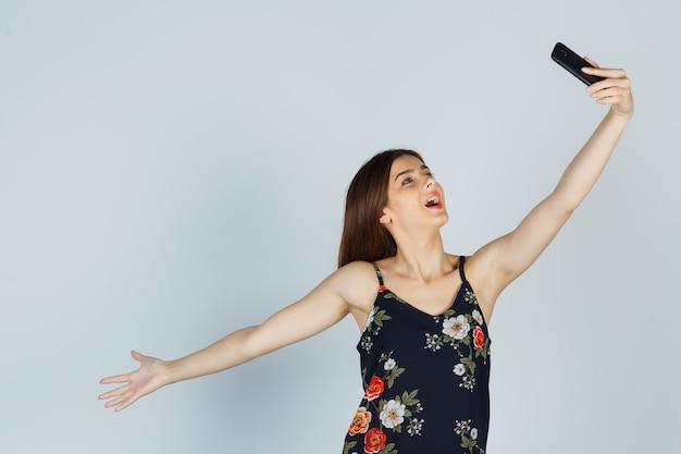 Jonge vrouw in blouse poseren terwijl ze selfie op smartphone neemt en er ontspannen uitziet, vooraanzicht.