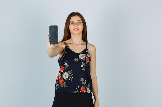 Jonge vrouw in blouse, rok die smartphone vasthoudt en er tevreden uitziet, vooraanzicht.