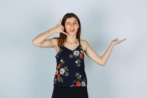 Jonge vrouw in blouse, rok die telefoongebaar toont, handpalm opzij spreidt, tong uitsteekt terwijl ze knippert en zelfverzekerd kijkt, vooraanzicht.