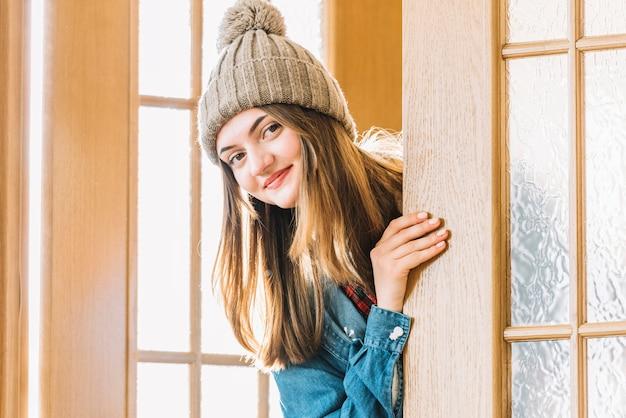 Jonge vrouw in bobble hoed die uit van deur gluren