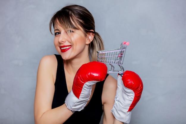 Jonge vrouw in bokshandschoenen met boodschappenwagentje op grijze achtergrond. zaklampstijl uit de jaren 90