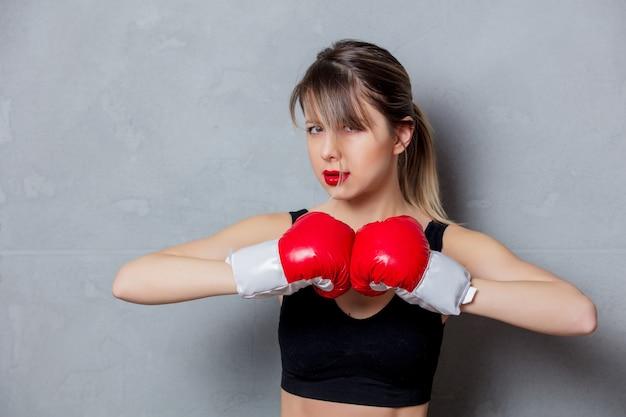 Jonge vrouw in bokshandschoenen op grijze achtergrond. zaklampstijl uit de jaren 90