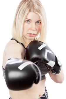 Jonge vrouw in bokshandschoenen. slagvaardigheid en moed. geã¯soleerd op witte achtergrond