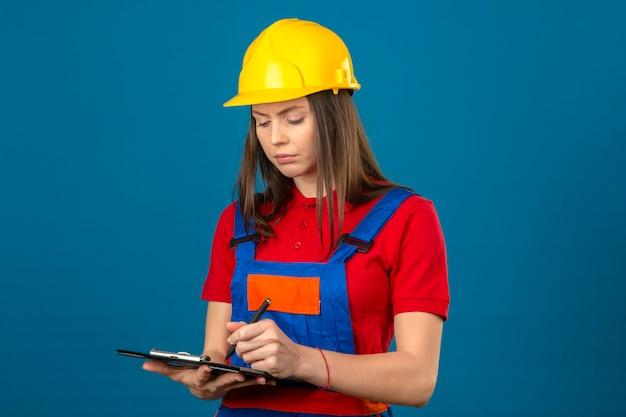 Jonge vrouw in bouw eenvormig en geel de holdingsklembord van de veiligheidshelm met documenten die rapport met ernstig gezicht schrijven die zich op blauwe achtergrond bevinden