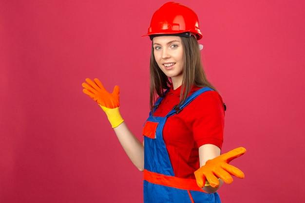 Jonge vrouw in bouw eenvormige en gele veiligheidshelm die zich met opgeheven wapens in handschoenen bevinden die op donkere roze achtergrond glimlachen