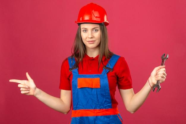 Jonge vrouw in bouw eenvormige en rode veiligheidshelm die en met vinger aan de kant glimlacht richt en regelbare moersleutel op donkerroze achtergrond houdt